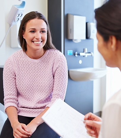 Woman in optometry office smiling at her optometrist