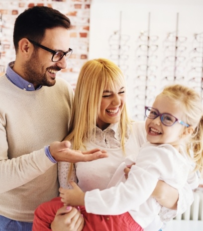 Mother and father smiling at daughter with new glasses