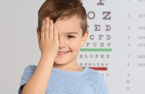Child with hand over one eye during eye alignment test