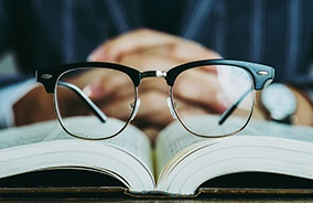 Pair of horn rim glasses resting on an open book