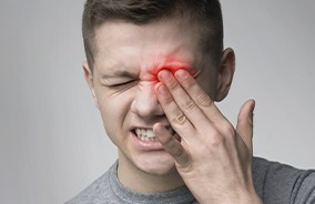 Teen with item stuck in eye holding his face