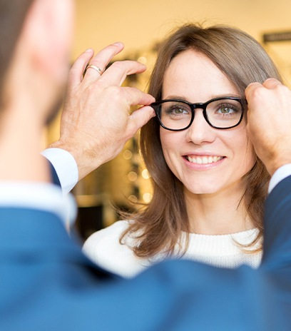 Optometrist helping woman choose the right glasses for her face shape