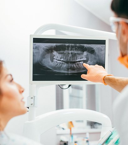 Dentist and patient looking at x-rays during preventive dentistry checkup